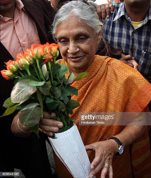Delhi Chief Minister Shiela Dikshit being presented a bouquet by a supporter at her residence in New Delhi