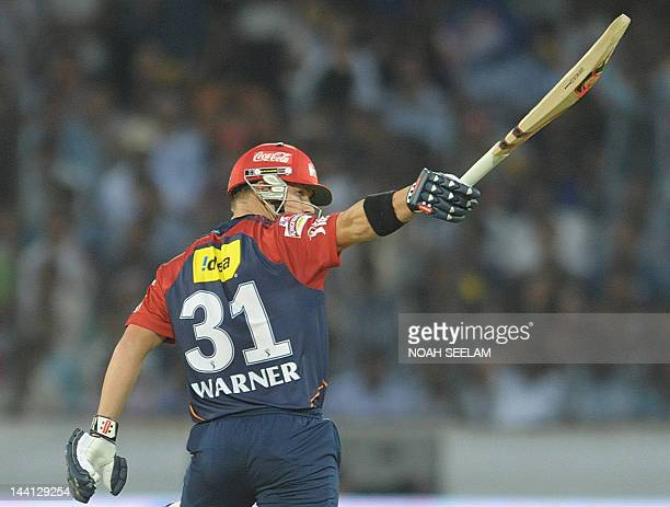 Delhi Daredevils batsman David Warner raises his bat after scoring a half century during the IPL Twenty20 cricket match between the Deccan Chargers...