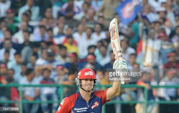 Delhi Daredevils player David Warner waves his bat after scoring a half century in 25 balls during the IPL Twenty20 cricket match between Kings XI...