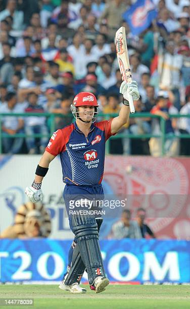 Delhi Daredevils player David Warner wavse his bat after scoring a half century in 25 balls during the IPL Twenty20 cricket match between Kings XI...
