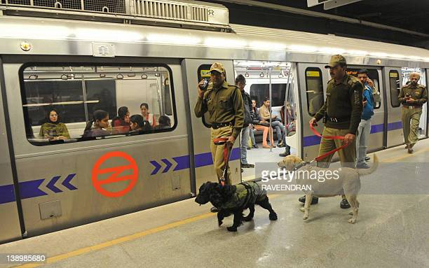 Delhi Metro passengers watch police personnel patrolling with sniffer dogs on a train platform at a metro station during a mock drill conducted by...