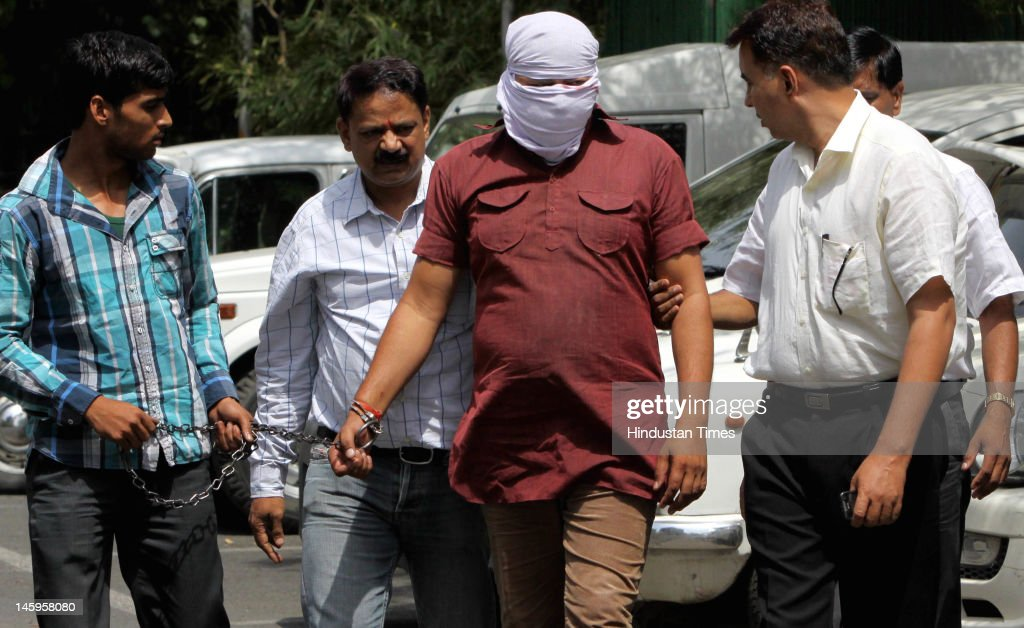 Delhi police lead Vinod Kumar Baliya (C), an alleged associate of the Manoj Bakkarwala gang, after he was arrested on June 8, 2012 in New Delhi, India. Baliya is accused of being involved in 13 cases of robbery and carjacking in Delhi, UP and Haryana.