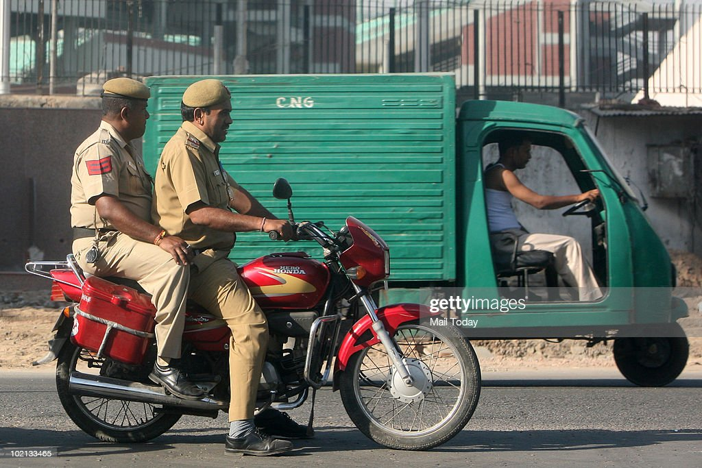Delhi Police Officers riding on a motorcycle without helmet violating the traffic rule.