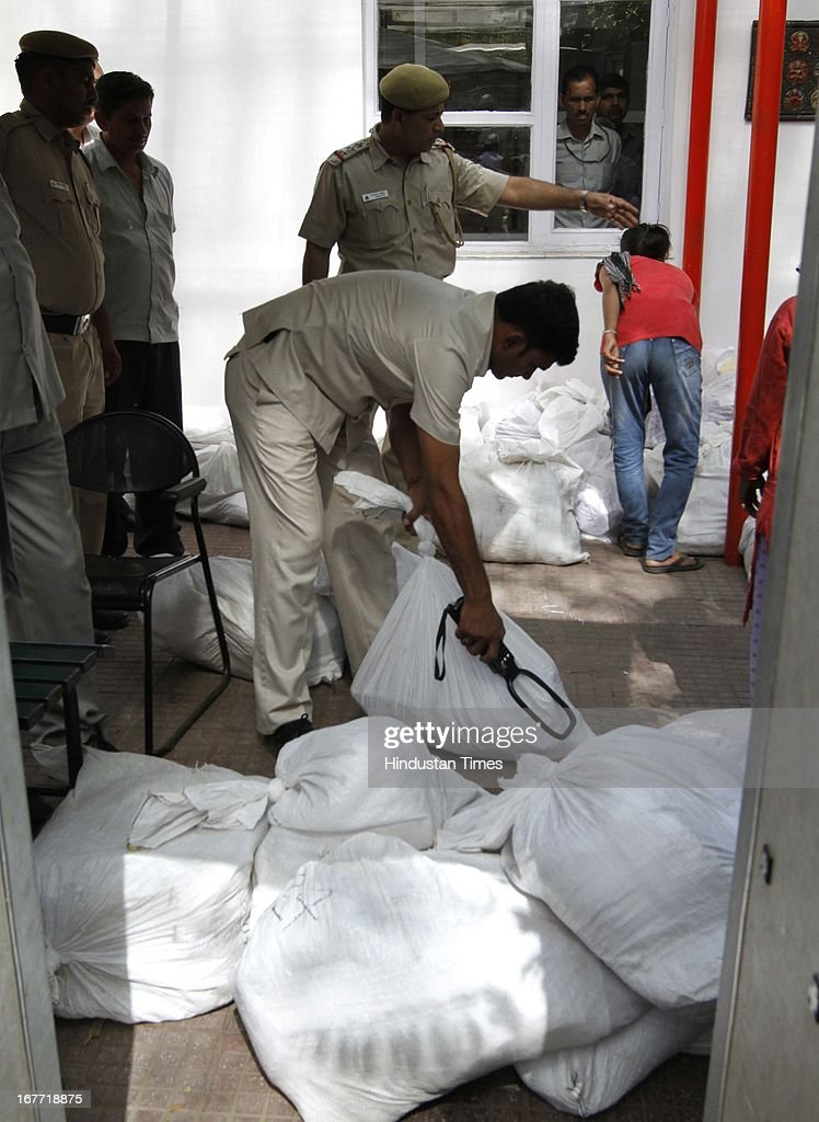 Delhi police personnel searching packets of letters after Aam Aadmi Party leaders submitted them at the residence of Delhi Chief minister, Sheila Dikshit on April 28, 2013 in New Delhi, India. The Arvind Kejriwal-led party decided to call off their march to residence of Delhi Chief Minister Sheila Dikshit after her office accepted to receive the 10.5 lakh letters written against inflated power and water bills.