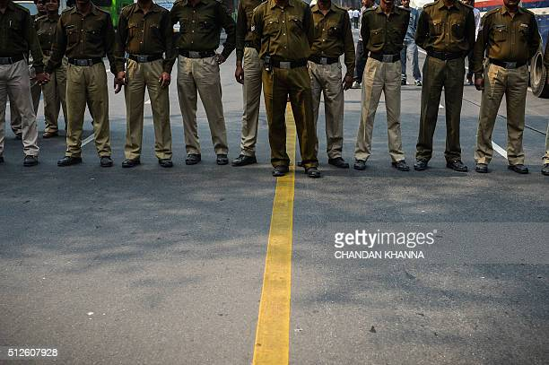 Delhi police personnel stand gurad as Indian activists from the Bharatiya Janata Yuva Morcha take part in a protest against the Congress party...