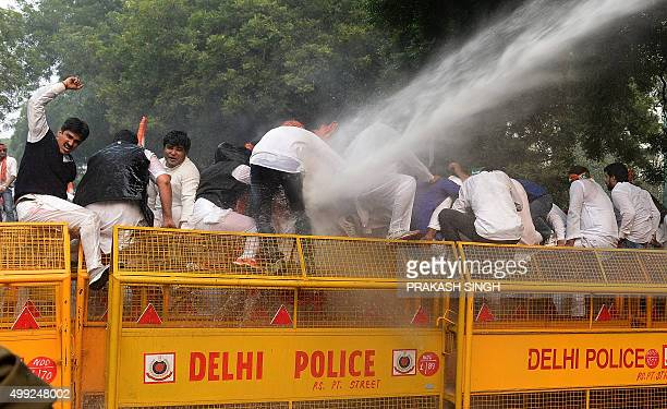 Delhi police use a water cannon to disperse activists of the Indian Youth Congress standing on a police barricade and shouting slogans against the...