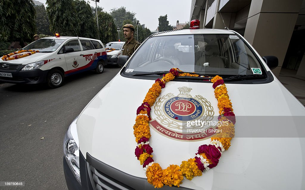A Delhi policeman stands next to newly inducted Police Control Room (PCR) vehicles during a flag off ceremony in New Delhi on January 20, 2013. In the wake of the recent gang-rape-cum-murder case, the Home Ministry recently gave approval for 370 new PCR vehicles in the capital and Delhi police are exploring new technologies to further enhance the performance of global positioning system-enabled 'Police Control Room' patrol vans by reducing their response time to distress calls. AFP PHOTO / Prakash SINGH