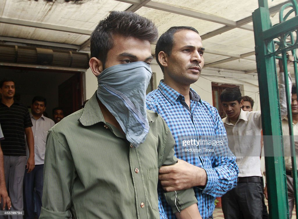 Delhi policemen escort an accused juvenile to a hearing of a murder case at the Juvenile Justice Board on August 7 2014 in New Delhi India A 19...
