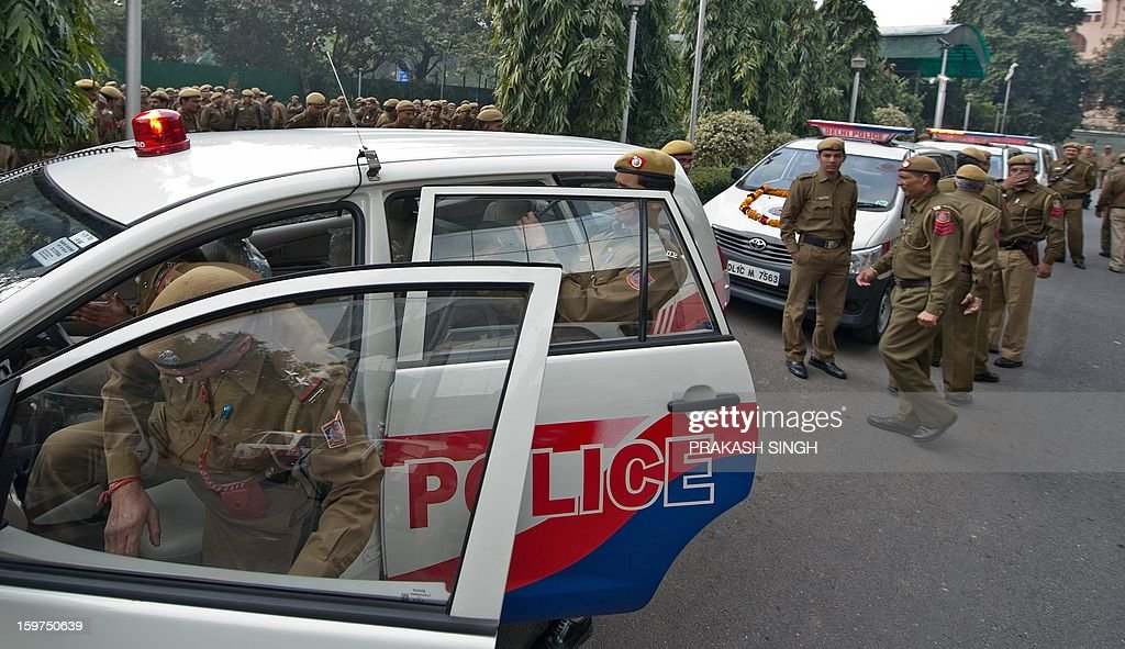 Delhi policemen stand next to newly inducted Police Control Room (PCR) vehicles during a flag off ceremony in New Delhi on January 20, 2013. In the wake of the recent gang-rape-cum-murder case, the Home Ministry recently gave approval for 370 new PCR vehicles in the capital and Delhi police are exploring new technologies to further enhance the performance of global positioning system-enabled 'Police Control Room' patrol vans by reducing their response time to distress calls. AFP PHOTO / Prakash SINGH