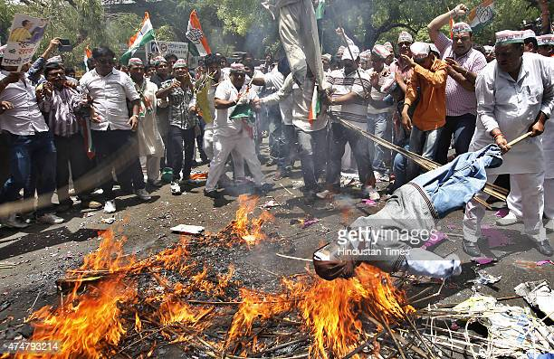Delhi Pradesh Congress Committee activists burn effigies of Prime Minister Narendra Modi on one year of his government during a protest at Jantar...