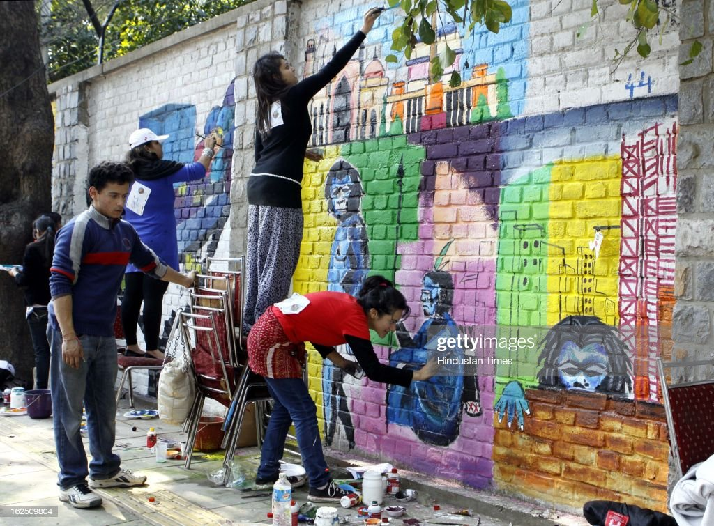 Delhi University students and NGO volunteers painting on the walls make 'Graffiti' at North Campus Delhi University on February 24, 2012 in New Delhi, India.