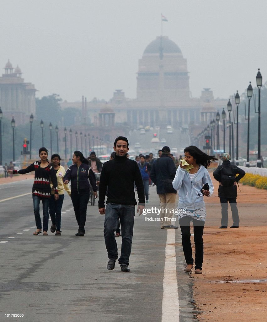 Delhites and tourist walks on Rajpath during the cloudy and pleasant weather on February 16, 2013 in New Delhi, India.