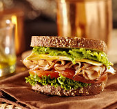 close up photo of a deli meat sandwich with turkey