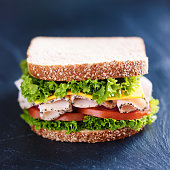 deli meat turkey sandwich on slate surface. Has cheese, tomato and green leaf lettuce on top of a whole wheat bread.