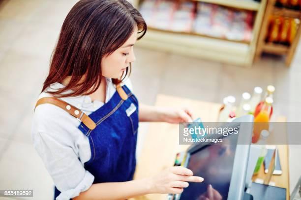 Deli owner entering credit card details in cash register