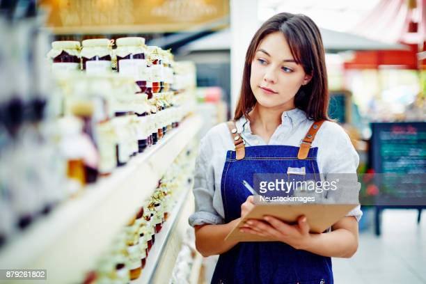 Deli owner holding clipboard and pen by shelves in store