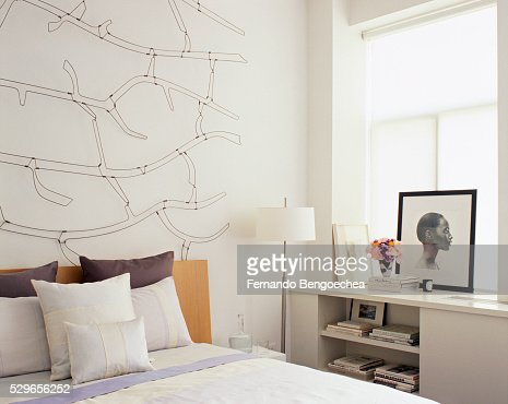 Hanging Photos On Wire delicate wire sculpture hanging on wall over bed stock photo