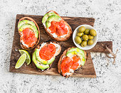 Delicious appetizers - cream cheese, smoked salmon and avocado sandwiches and olives on a wooden board. On a light background, top view