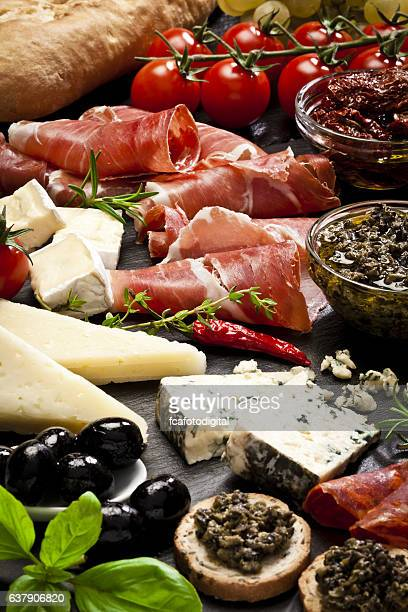 Delicious appetizers on dark slate table