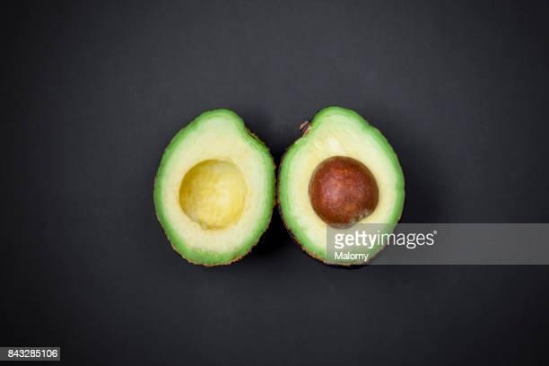 Delicious avocado on black background. Greenery