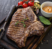 Delicious beef steak on black stone table, close-up.