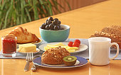 breakfast table with coffee, milk, wholegrain bun and bread, coissants, fruits, butter and marmalade