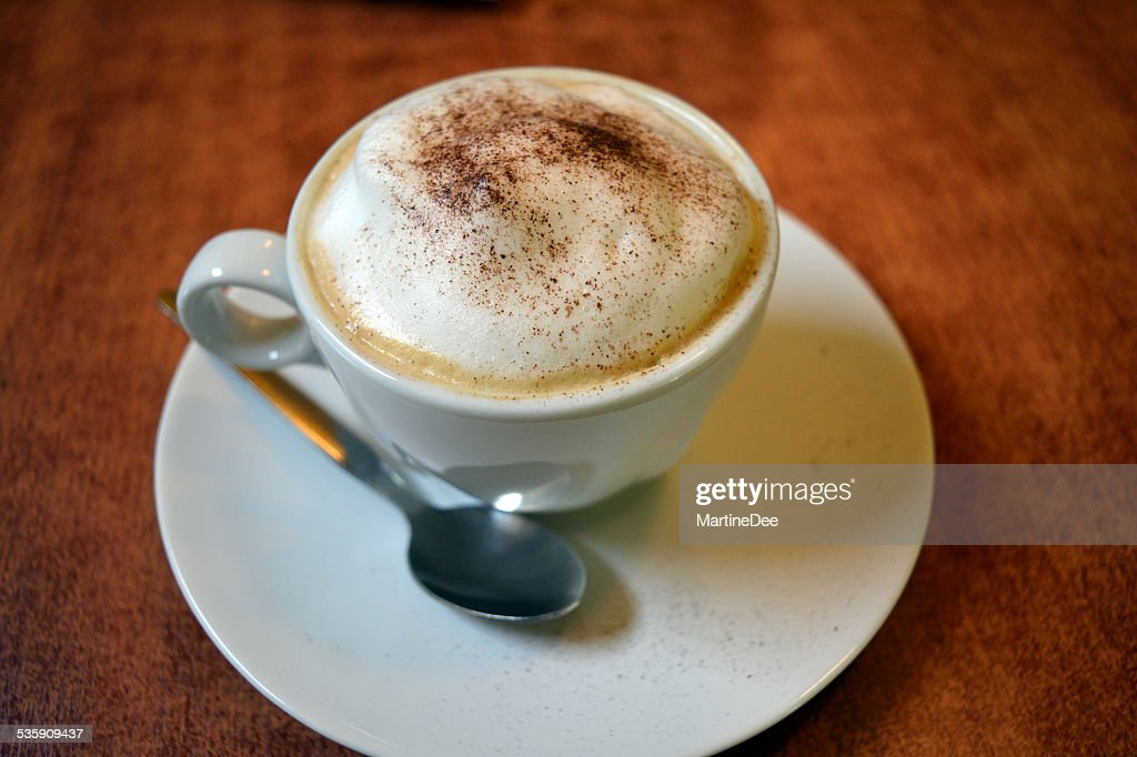 Delicious cappuccino in white cup on the wooden table : Stock Photo