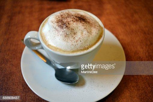 Delicioso cappuccino em copo branco na mesa de madeira : Foto de stock