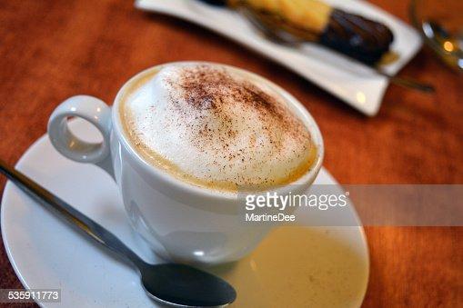 Delicioso cappuccino en blanco y taza en mesa de madera : Foto de stock