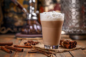 Large glass of delicious chai latte with a sprinkle of cinnamon