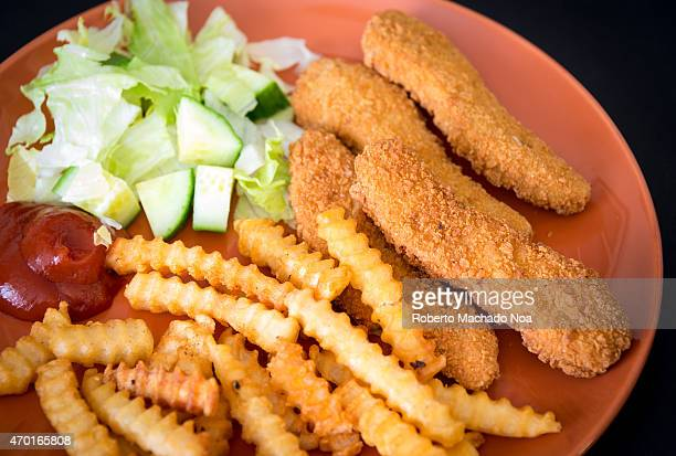 Delicious chicken fingers or chicken nuggets with french fries and a little salad as side dish traditional kid's meal