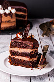 Delicious dark chocolate cake in white plate on wooden table background