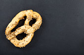 Fresh baked delicious crispy twist with sunflower seeds on black background