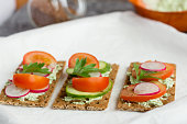 delicious diet sandwiches with cottage cheese with herbs and vegetables on a white background