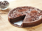 A whole chocolate cake dusted with cocoa and cocoa nibs with one slice missing.