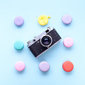 delicious French dessert macarons with vintage camera on a blue background