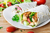 Delicious fresh chicken wrap, closeup shot. Tasty tortilla with salad and turkey meat,healthy eating scene.