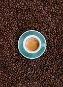 Delicious fresh morning espresso with a beautiful crema in a ceramic green cup with a saucer on the coffee beans background, top view