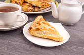 Delicious golden triangles of puff pastry on the table and a cup of tea - top view