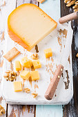Delicious dutch gouda cheese with cheese blocks, crackers, walnuts and special knife on oud wooden table.