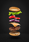 Delicious hamburger with flying ingredients on black background