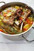 kjotsupa -  delicious Icelandic Lamb winter hot Soup in a stainless steel casserole pan on wooden table, authentic recipe, vertical view from above, close-up