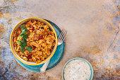 Delicious Indian biryani with cucumber raita side dish, top view, blank space