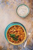 Delicious Indian boneless chicken dum biryani with cucumber raita side dish. Top view, blank space