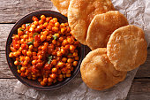 Delicious Indian Chana masala and puri bread close-up on the table. Horizontal top view