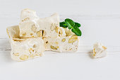 Delicious traditional Italian festive torrone or nougat with nuts on white wooden background with place for text. Soft nougat blocks with almonds with fresh mint leaves. Italian sweets. Copy space.