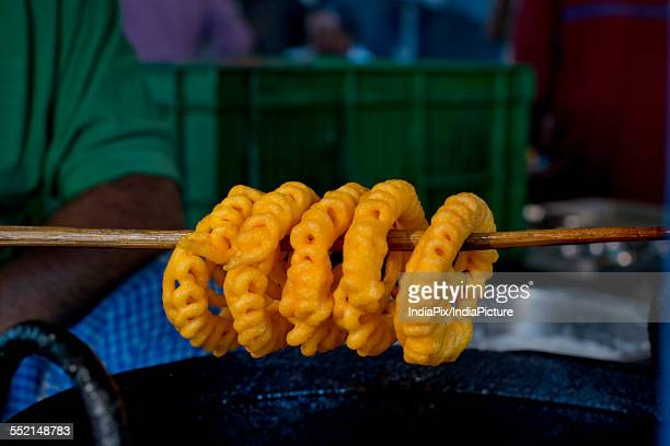 Delicious jalebis hanging on stick at stall