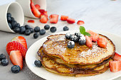 Four delicious, hot Pancakes. Self made with Bananas, Coconut and eggs. Garnished with Strawberries, Blueberries, Icing Sugar and Maple Sirup. All Pancakes are on a white plate and next to them lie tw