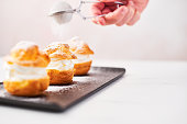 Sprinkling powdered sugar over delicious cream puff cakes on a black plate on white marble table over pink background. Selective focus, copy space.