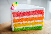 Slice of rainbow cake, Delicious rainbow cake on wood plate.